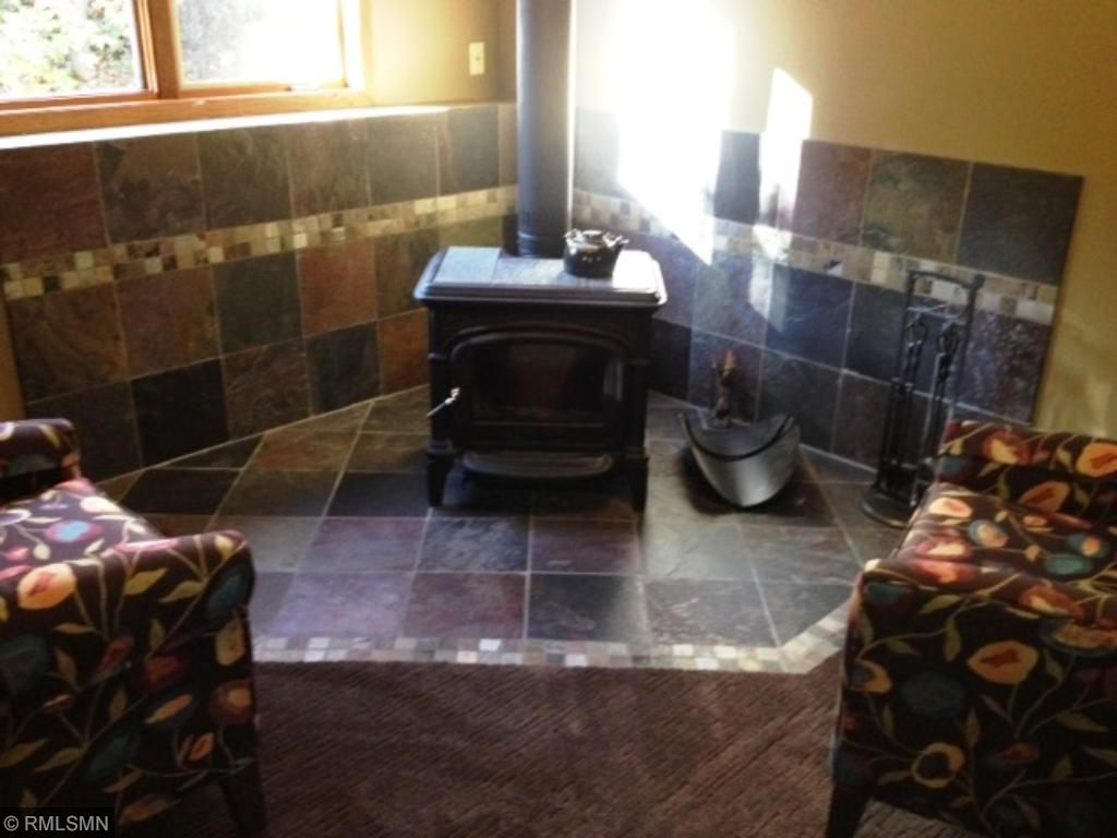 Free standing wood burning stove in family room with beautiful surround.