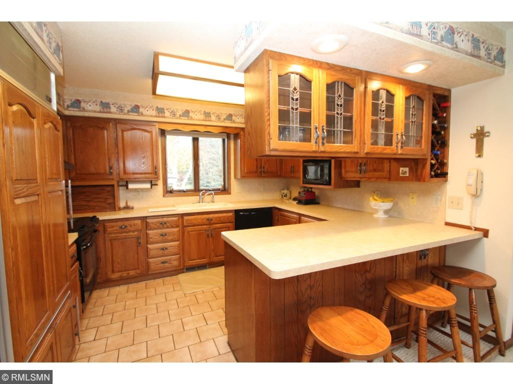 Kitchen features a breakfast bar and top of the line Sub Zero refrigerator.