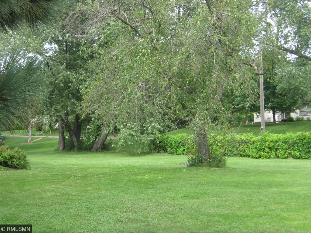 fabulous 1 acre yard that is lined with a hedge and landscaped with flowers and mature trees