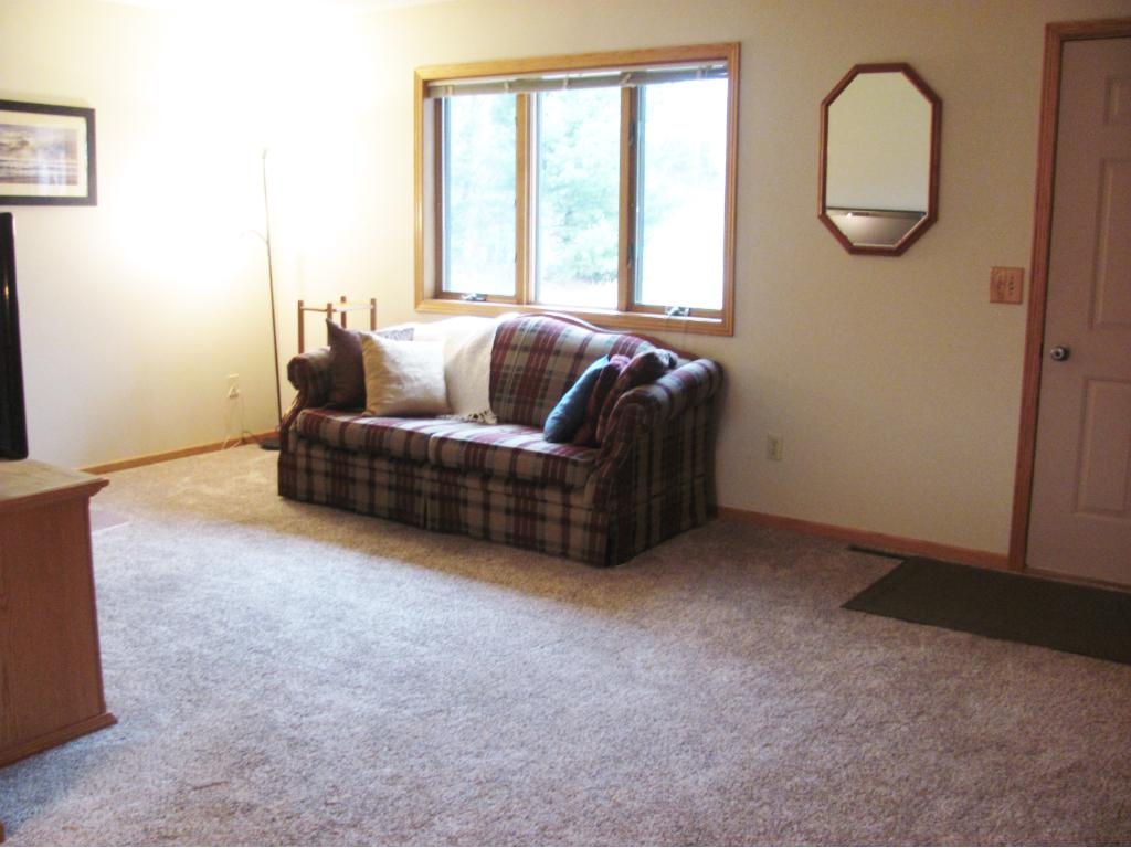 Sun filled living room with bay window.Freshly painted walls and new carpet.
