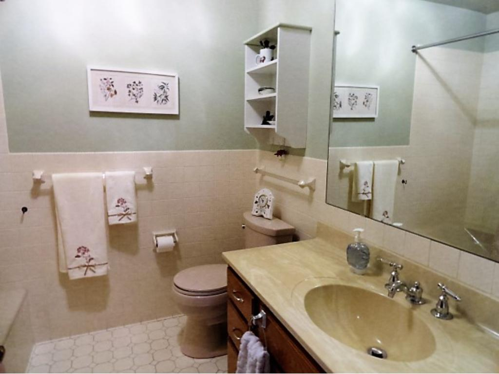 The main bath is spacious and offers a large soaking tub with grab bars, tiled shower/bath tub area and half of the bathroom walls, tile floors, raised toilet, newer faucet fixtures, large vanity and linen closet.