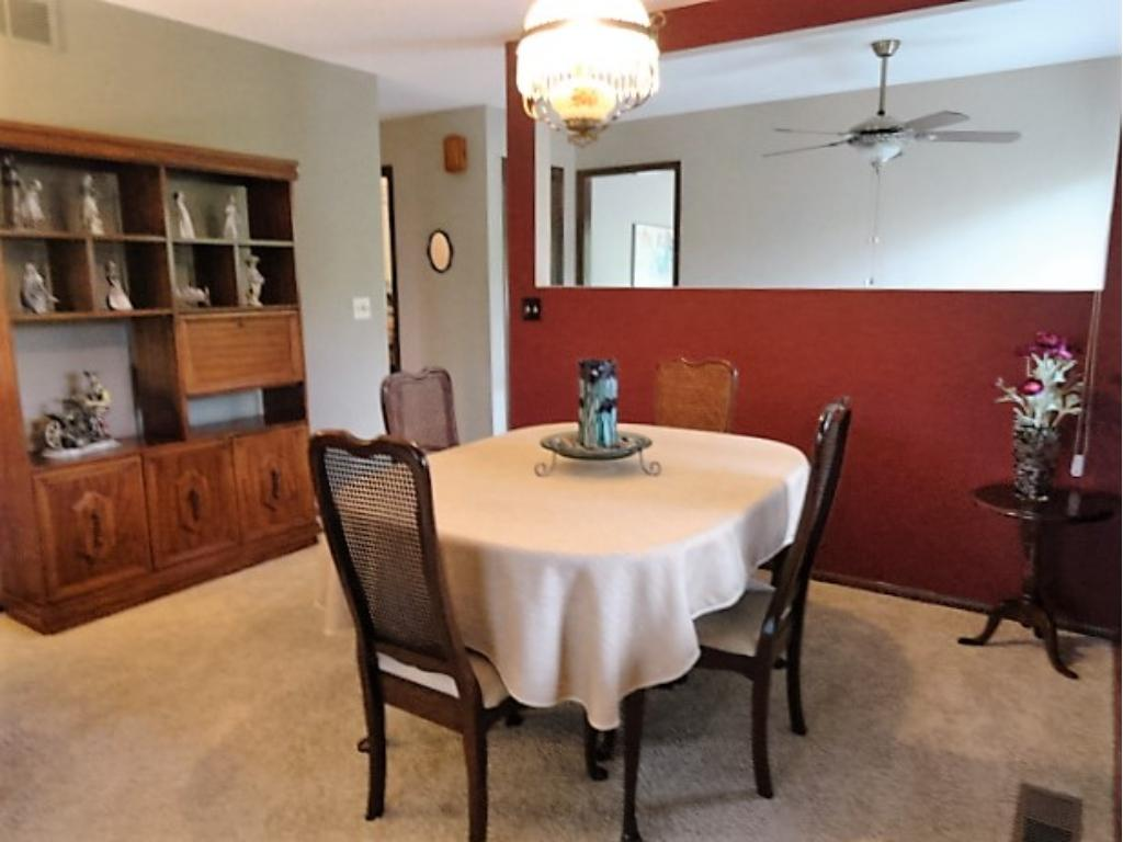 Formal dining area is open to the formal living area allowing an expansive table for large gatherings. Exterior views through 3 season porch, large specialty window in entry,  and bay window in LR.