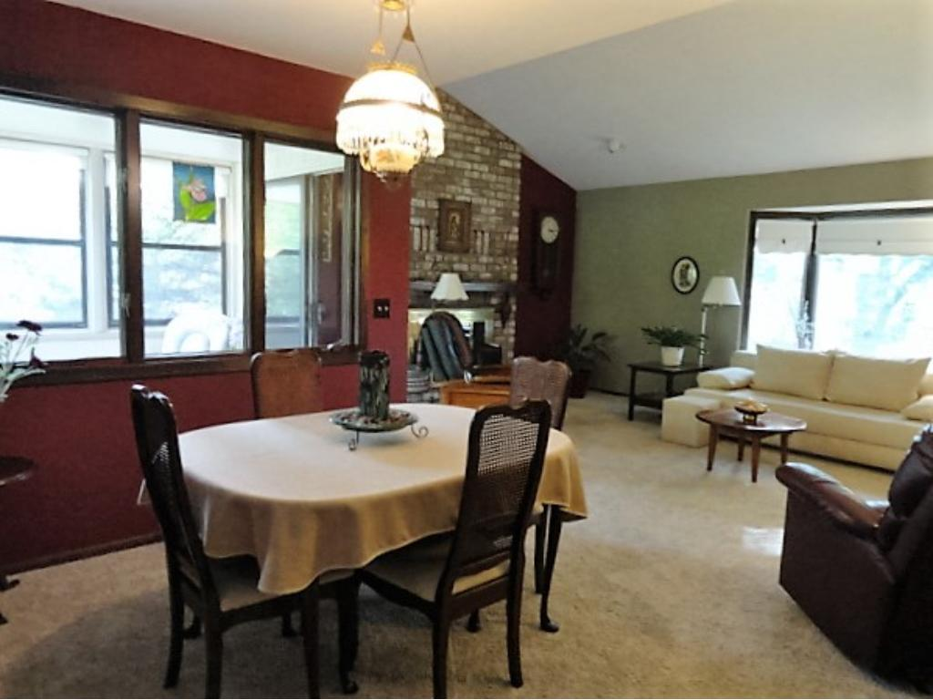 Dining room with views of the living room and 3 season porch. Over head light in DR, upgraded carpet in neutral tones.