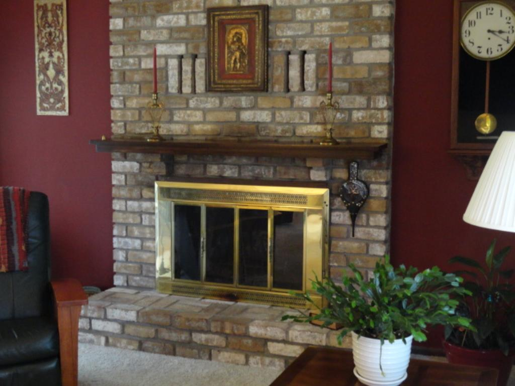 Nicely appointed wood burning, brick fireplace with raised hearth and mantle.