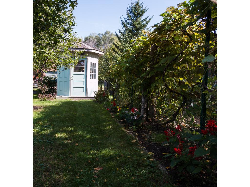 "An adorable ""pintrest-y"" garden shed anchors the yard's back corner and houses garden tools and off-season planters."