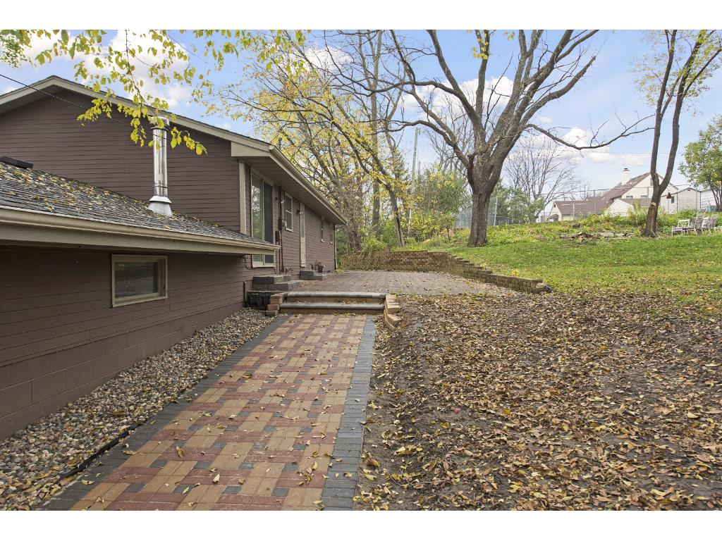 Back of home as you walk around garage to paver walkway and paver patio.