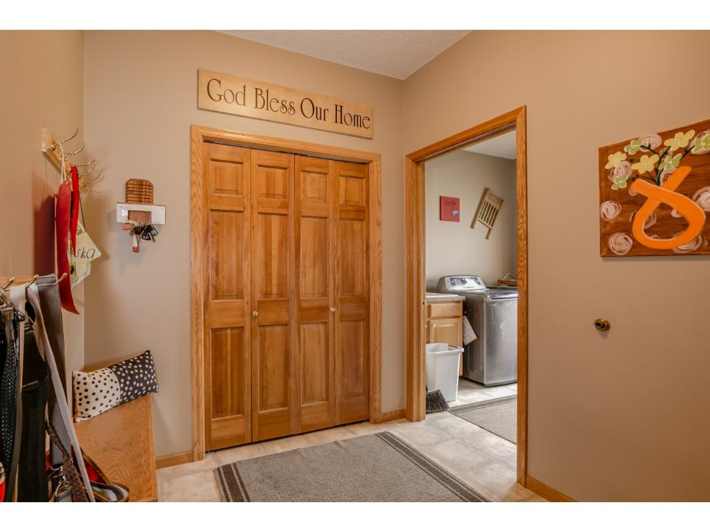 Large mudroom off garage with bench and additional storage closet.  The laundry room has built in cabinets with a utility sink and an oversized window! Easy care vinyl flooring throughout both rooms.   Now you don't have to dread the laundry!
