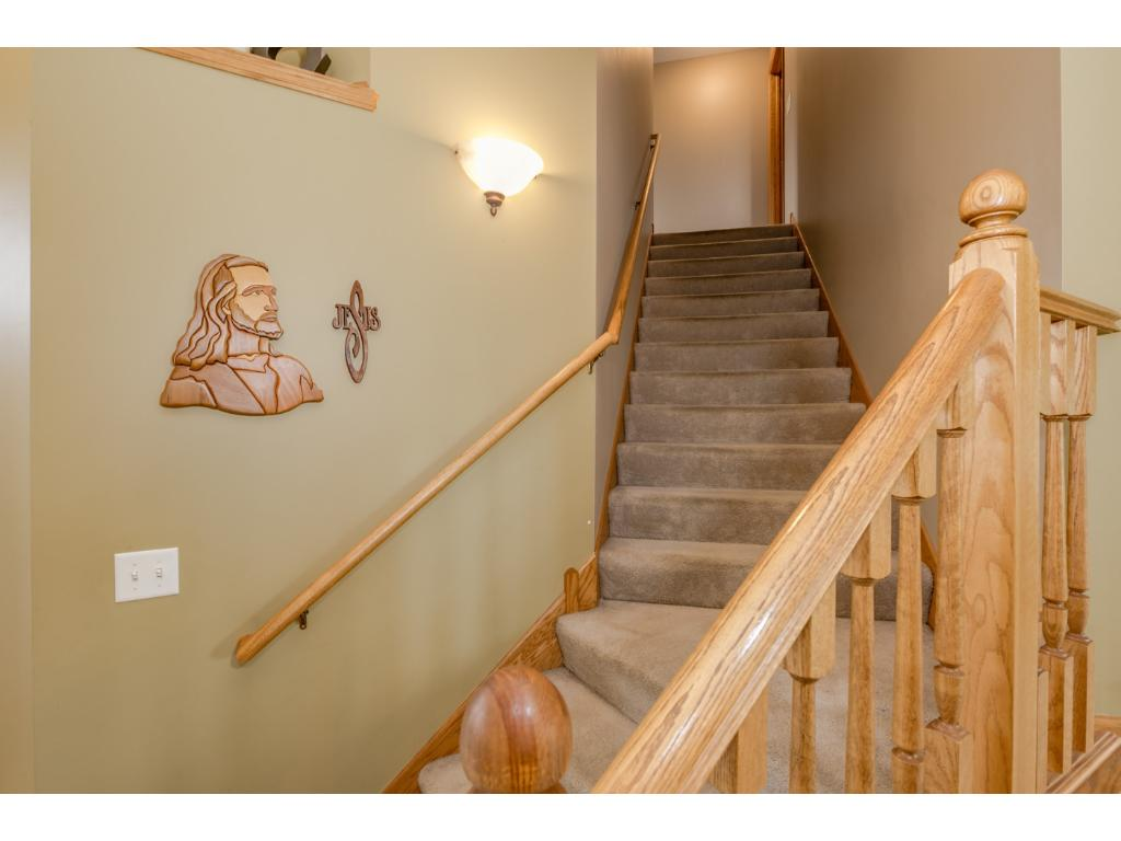 Open stairwell to upper level.  The upper level has four bedrooms and two full bathrooms.
