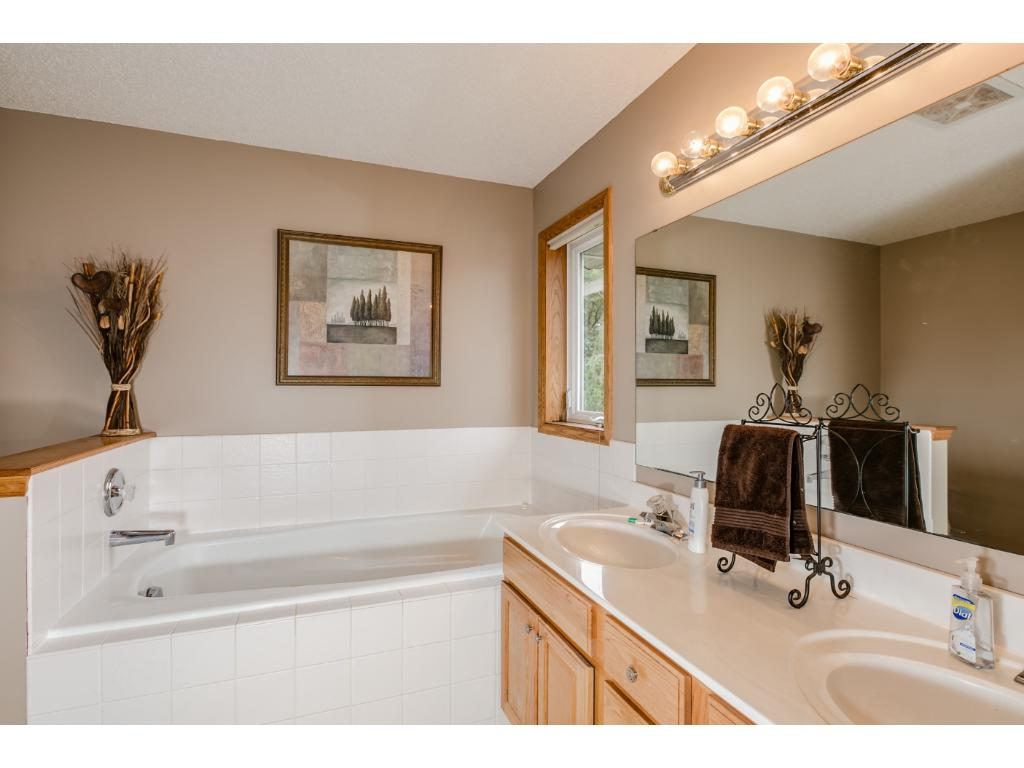 En suite bath has solid surface counter top, dual sinks, soaking tub with tile surround,stand alone shower and an additional linen closet.