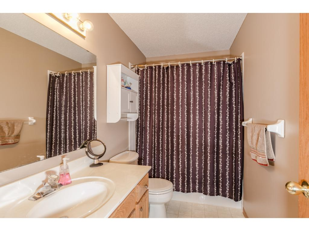 The full bath has easy care vinyl flooring, solid surface counter top, tile surround tub and shower and hardwood cabinets.
