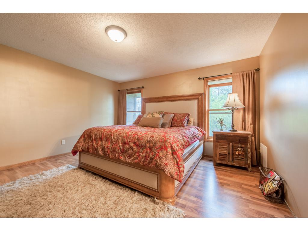Spacious owners' suite on the upper level has 2 tall windows flanking the bed.