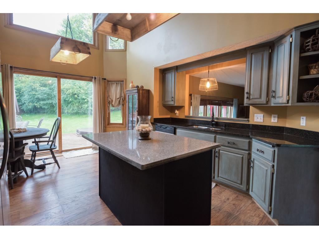 The kitchen has refinished cabinetry and an island topped with granite.