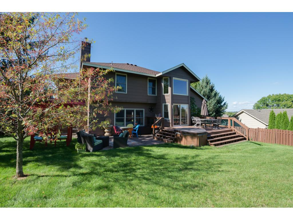 This photo shows the back of the house. The backyard has a patio, deck, hot tub and plenty of room for playing!