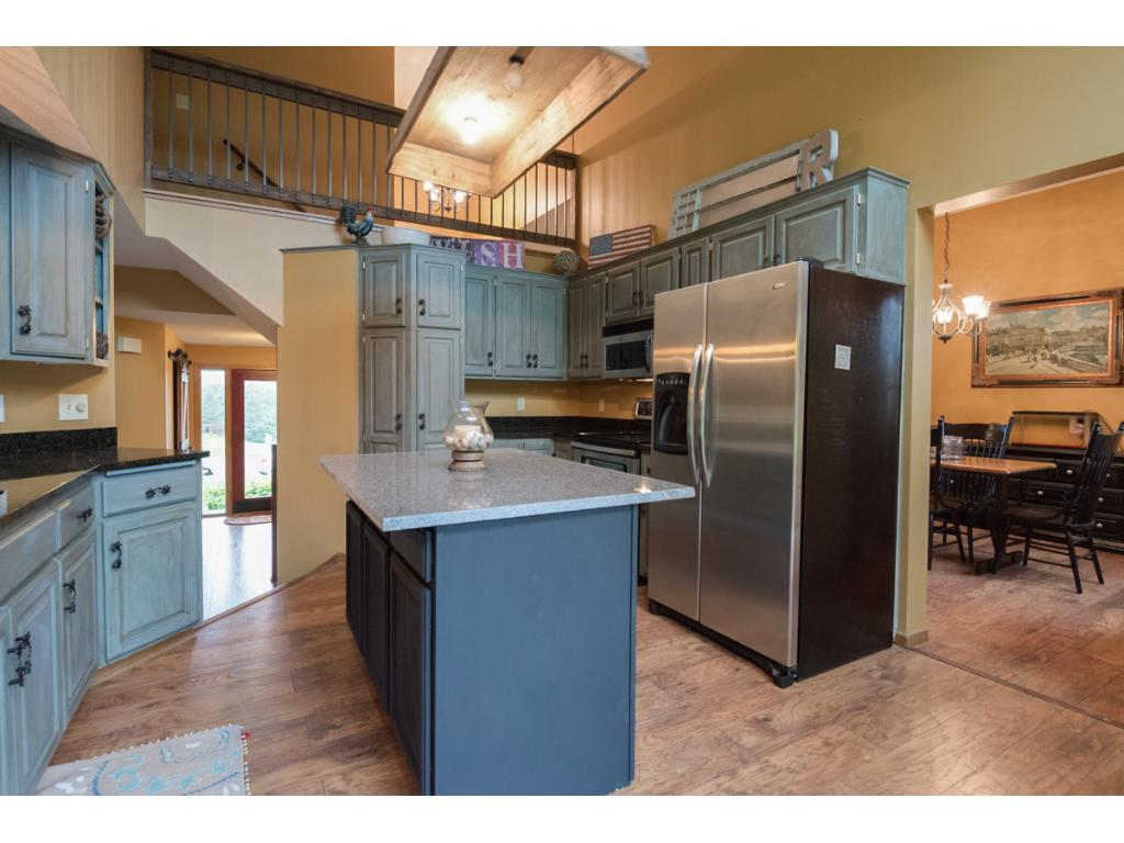 The kitchen features stainless steel appliances and granite on the perimeter countertops as well as the island.