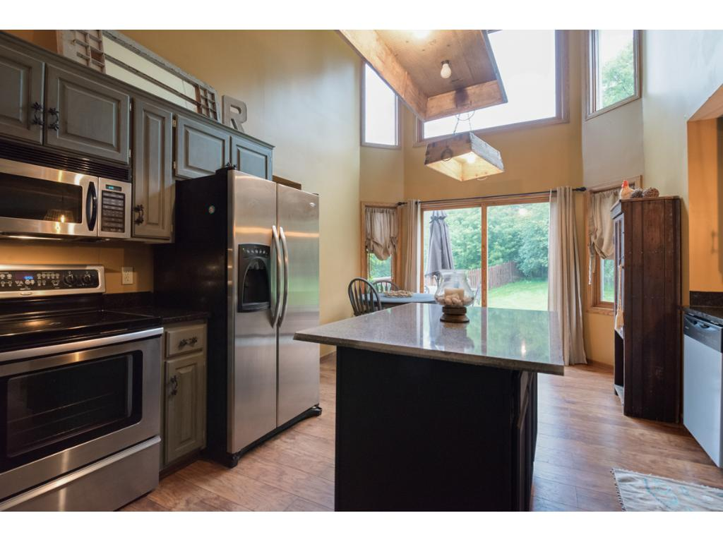 Open to the 2nd story, the kitchen is highlighted with windows soaring all the way up to bring in the light.