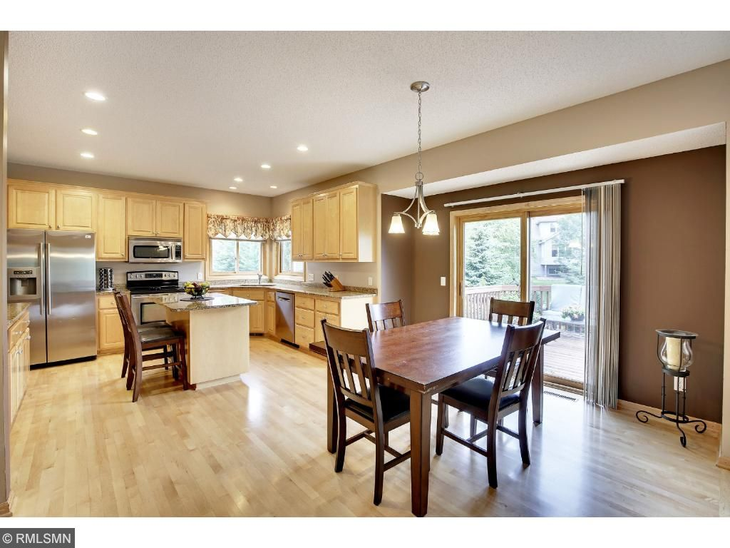 Informal dining room leads to deck and gorgeous custom designed patio with fenced backyard.