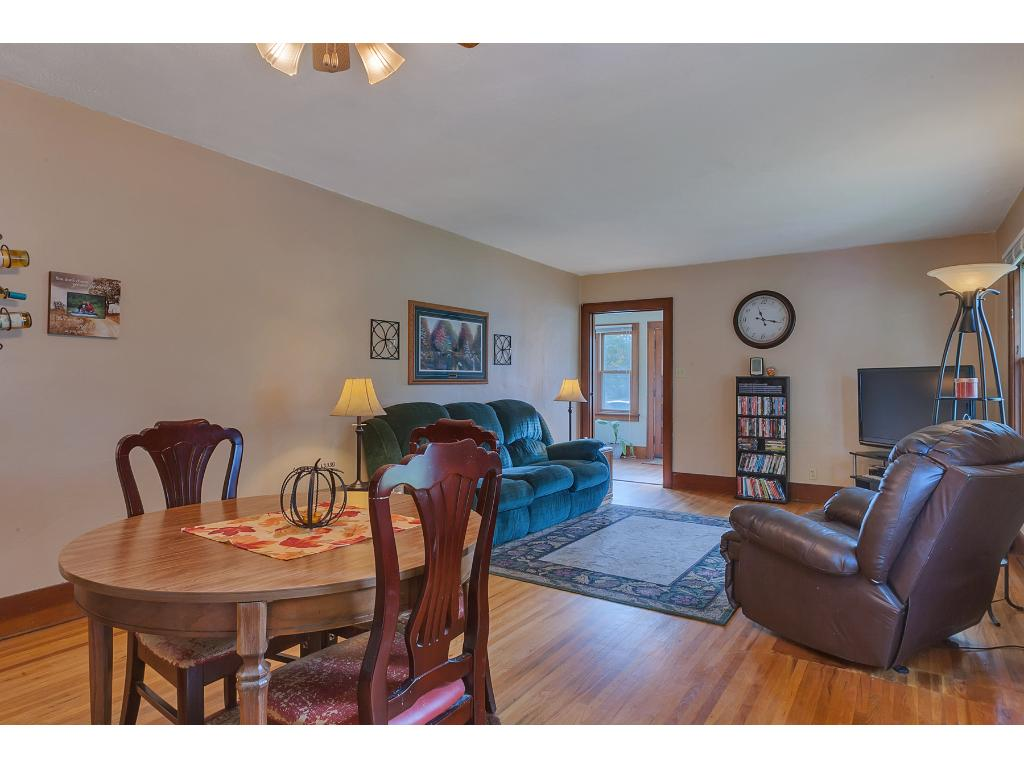 The dining room has a ceiling light fan fixture and hardwood floors.