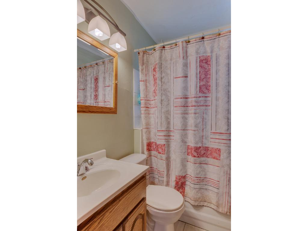Full bath on the main level that features tiled flooring and a shower/tub surround.