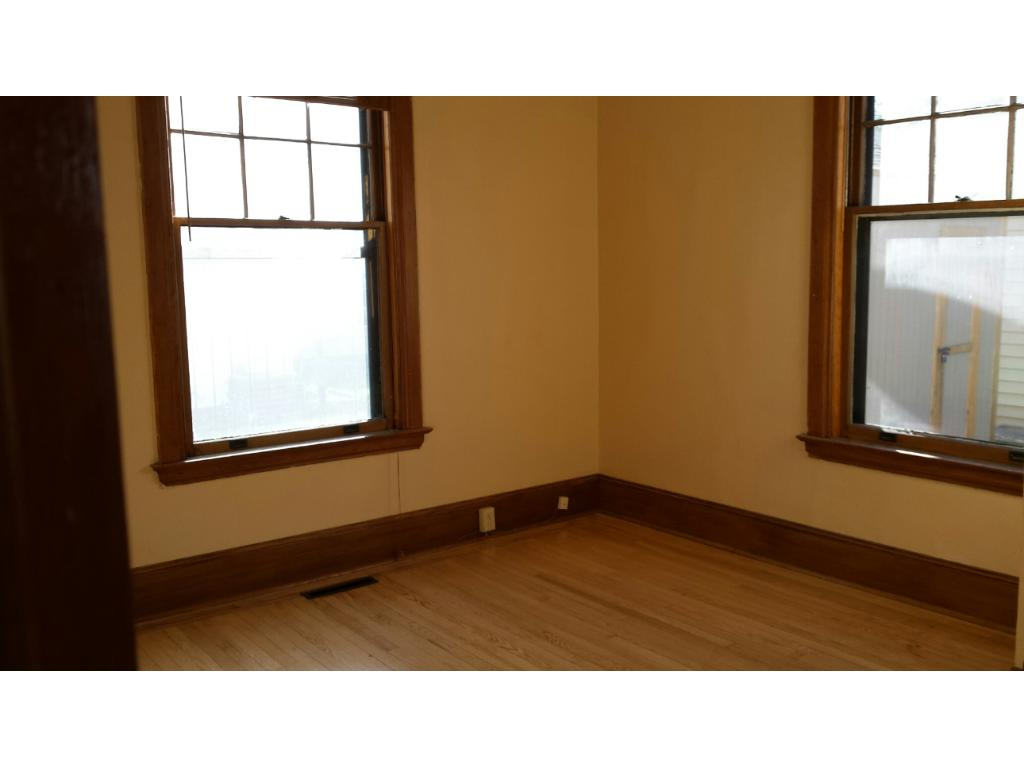 BEDROOM WITH REFINISHED GLEAMING HARDWOOD FLOORS AND DOUBLE FRENCH DOORS OFF OF HALLWAY ON MAIN LEVEL OF DUPLEX