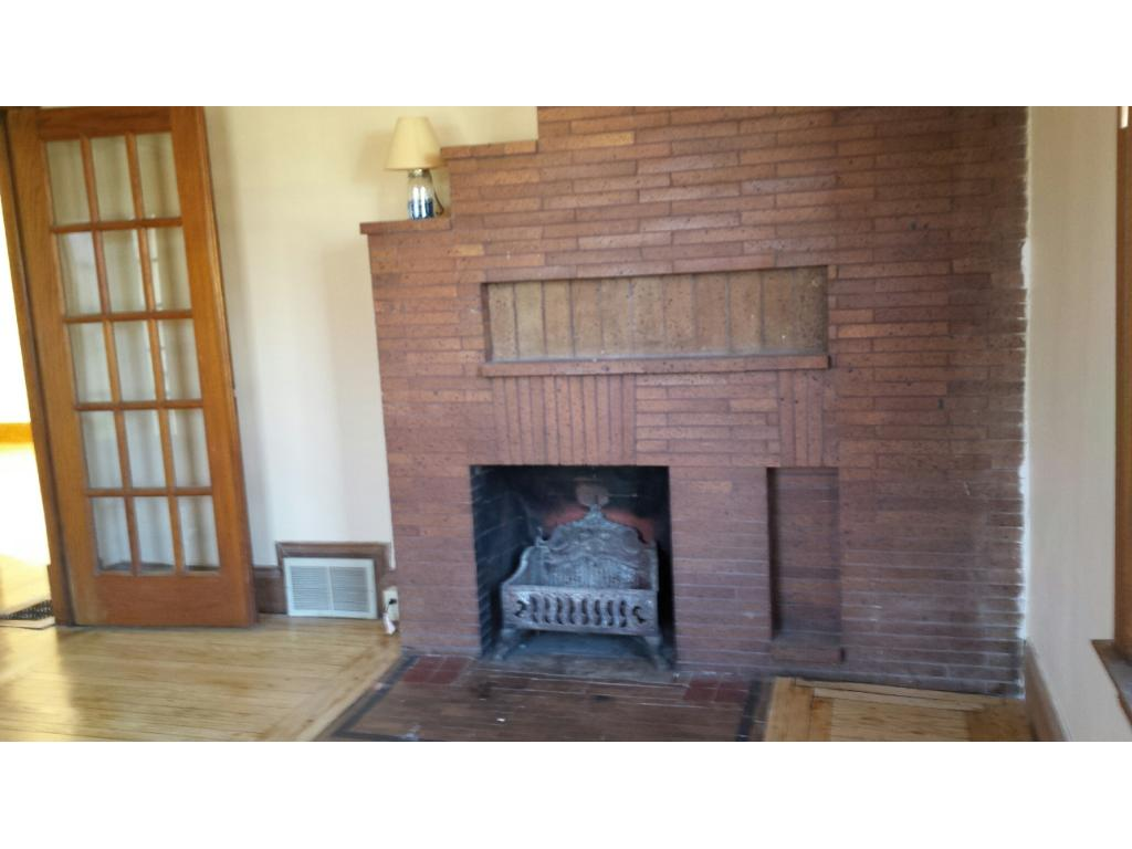 1ST FLOOR LIVING ROOM HAS A FIREPLACE WITH BRICK SURROUND AND REFINISHED GLEAMING HARDWOOD FLOORS