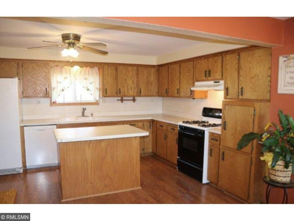 The spacious kitchen has a center island breakfast bar, wood laminate flooring, plenty of counter space and all appliances stay.