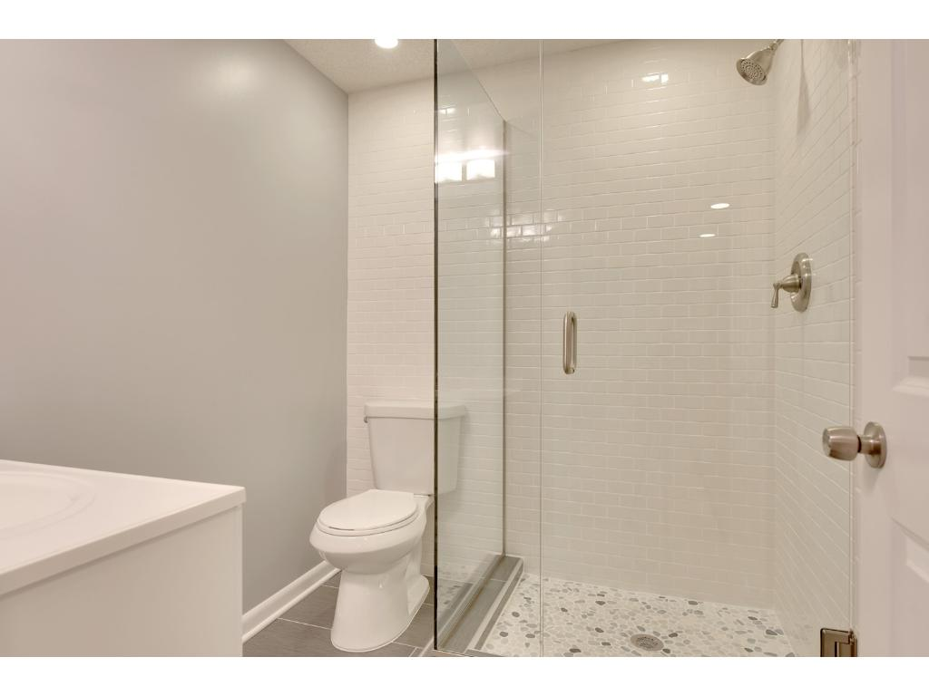 Brand new lower level bathroom with glass shower, tiled floors and accents - beautiful and a must see!