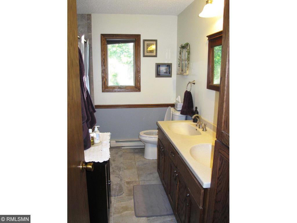 Main floor bathroom with new cabinets, flooring & tiled tub/shower.