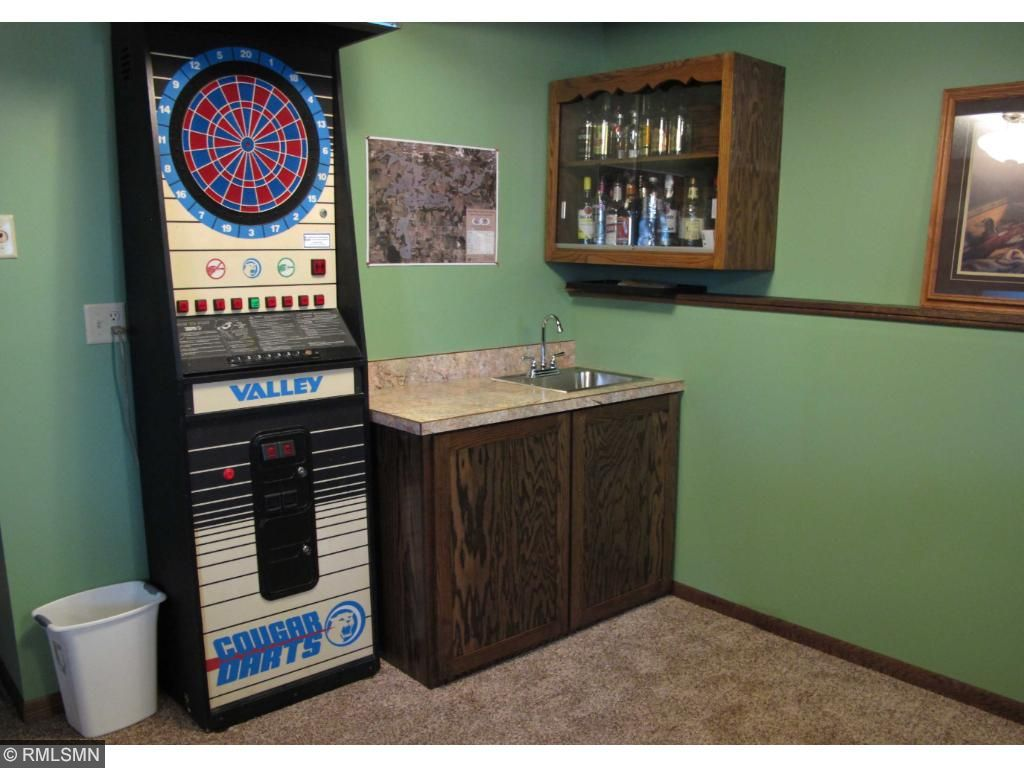 Custom built wet bar has room in cabinet to fit a small refrigerator.