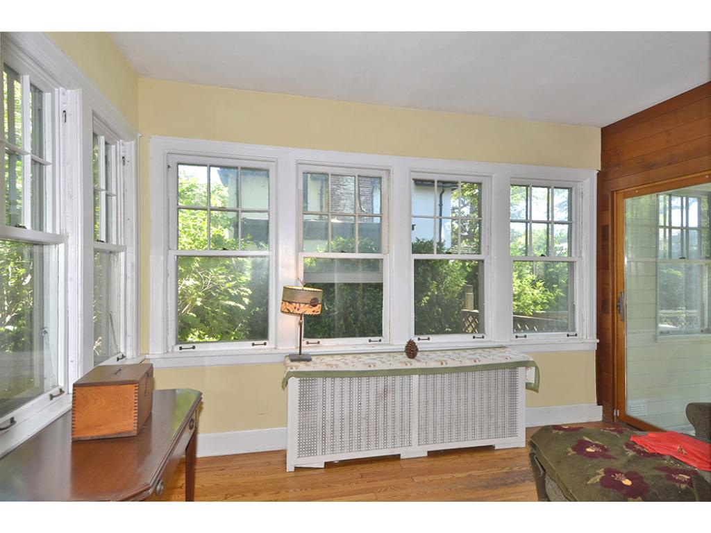 The Sun Room is surrounded with windows and opens to an enclosed mud room/porch at the back of the home.