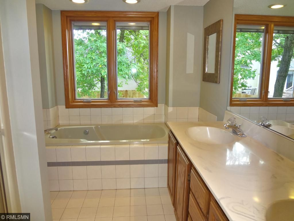 Ensuite master bath with two sinks, walk-in shower, and tub.