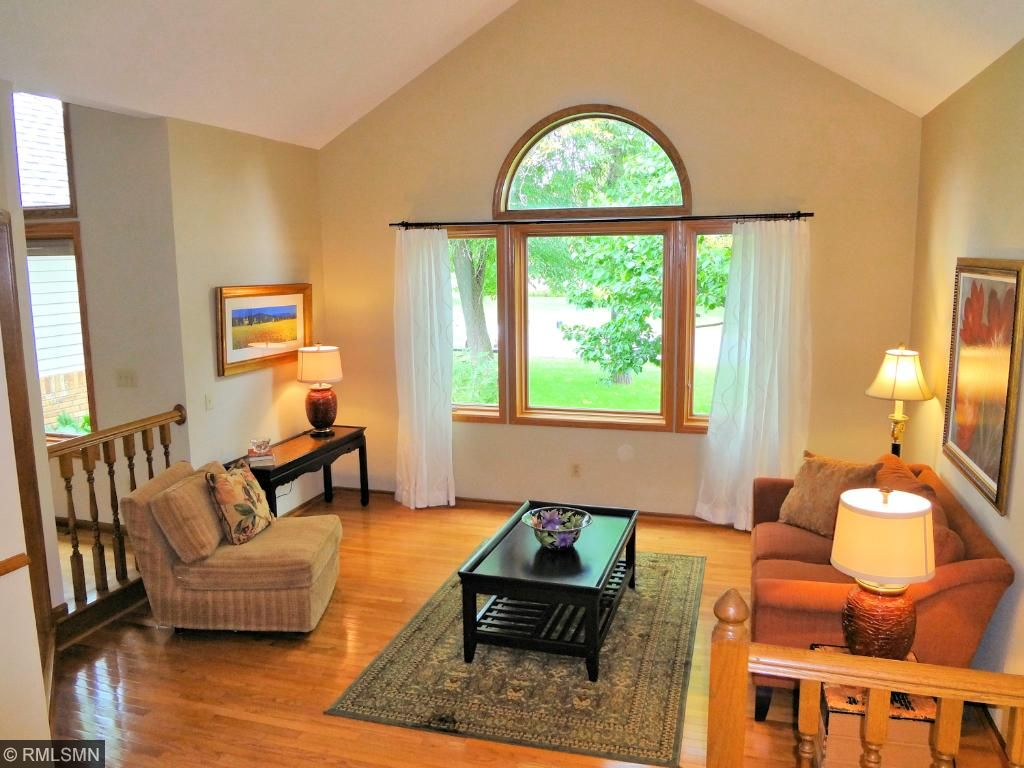 Sunken living room has dramatic vaulted ceiling and large Pella windows for nature views.