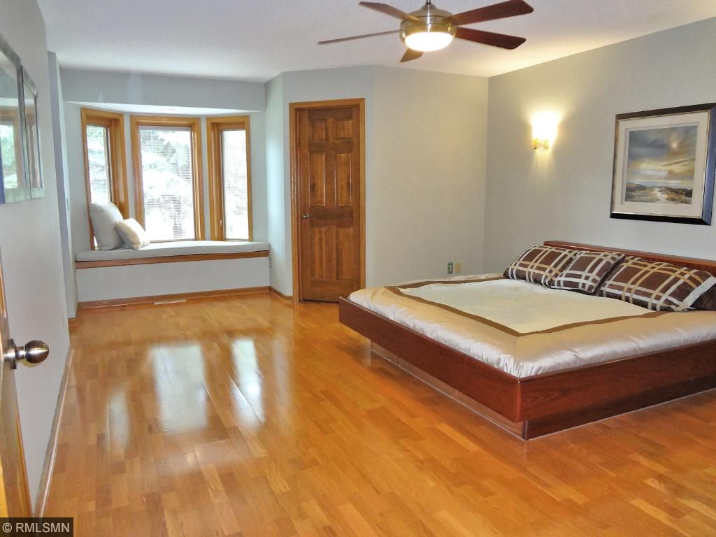 Large owners with natural hardwood floors and sconce lighting.