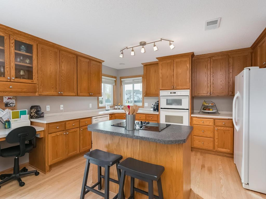 Large kitchen features center island with cook top, large pantry, tons of cupboards, wood floors, wall oven