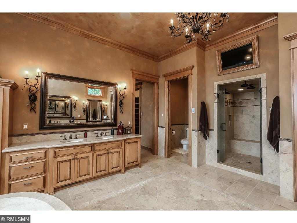 View of stone soaking tub and granite vanity. Tile floors with in-floor heat. View of lake with mechanical blinds.