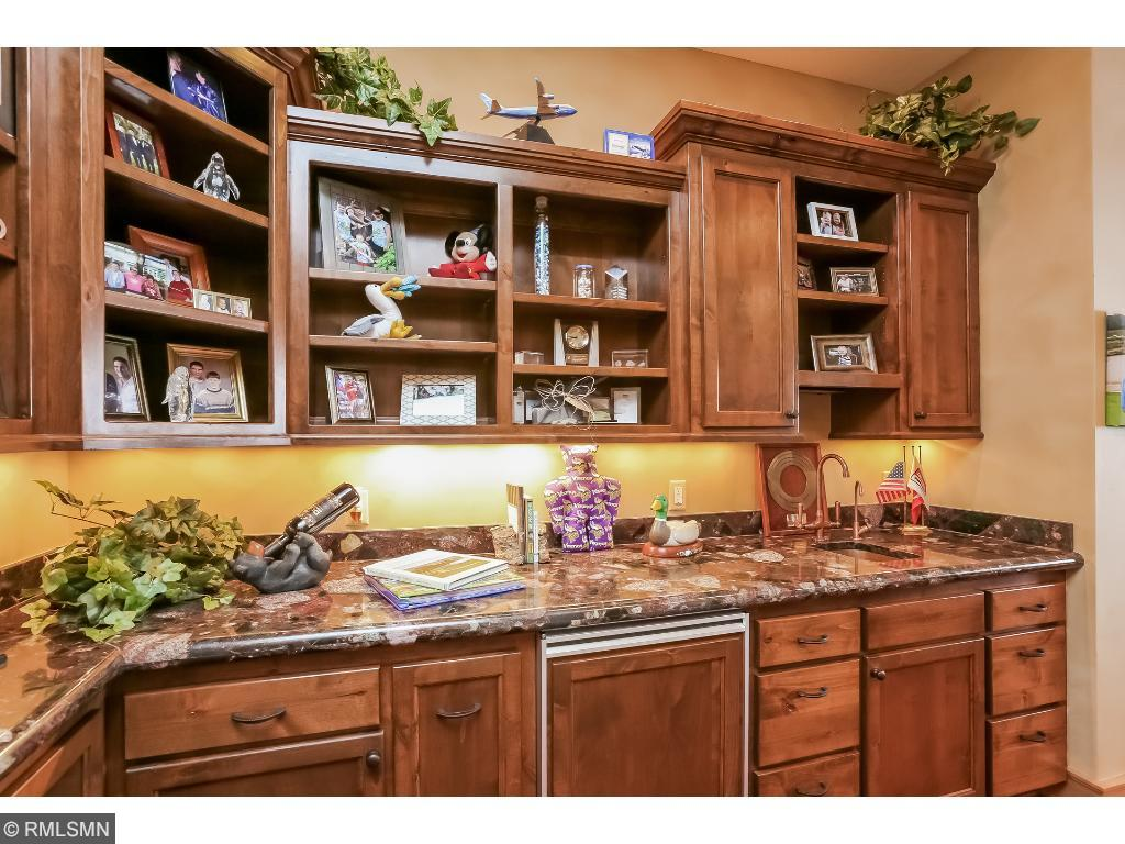 Hardwood cabinetry with stained glass and secure doors to wine storage area.