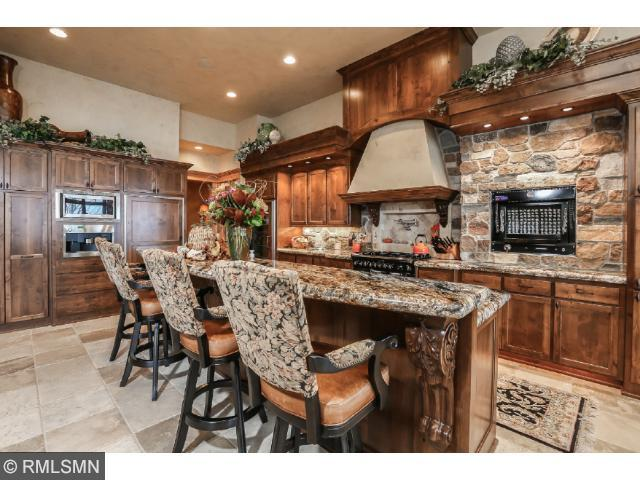 Just off the great room is this custom bar with granite countertops, hand carved fish scene on patrons side with glass top. Under the counter high end appliances including ice maker and dishwasher.