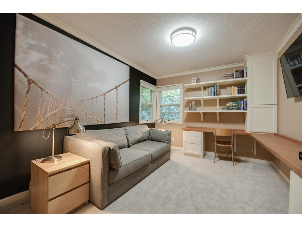 Main level bedroom offers brand new carpet & amazing custom built-in desk w/ shelving & cabinetry for storage!