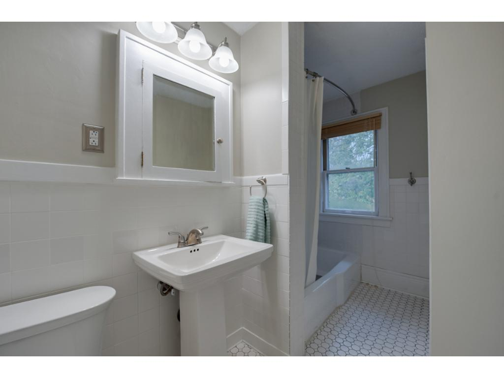 Another full bath! Updated w/ classic white pedestal sink & medicine cabinet above, tile floor & surround & tub/shower combo.