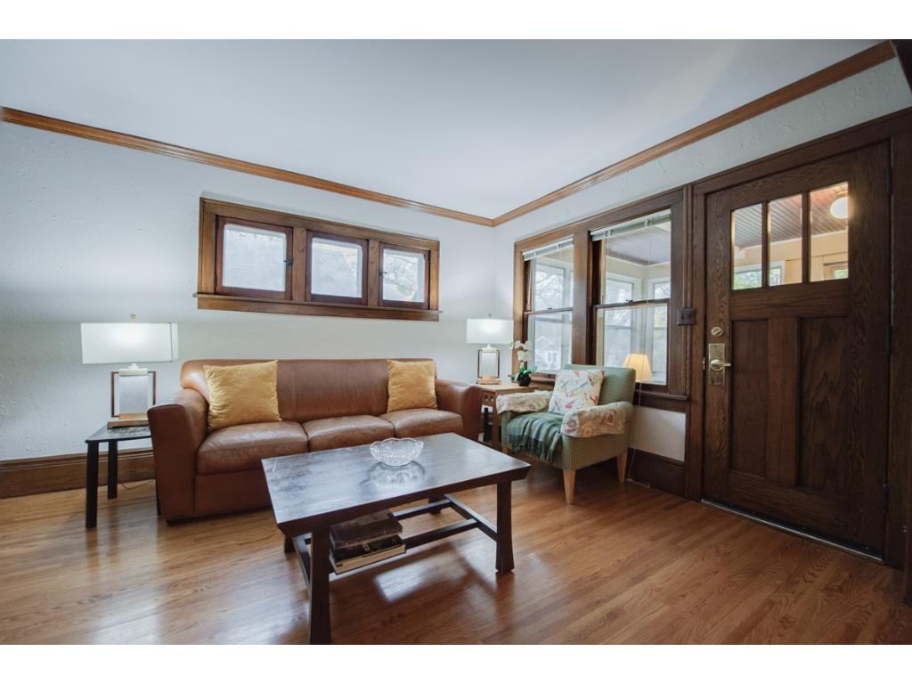 """Gorgeous living room presents oak hardwood floors, 10"""" baseboards & crown molding details that extend thru-out the main level. Also showcased is the original piano windows & oak staircase."""