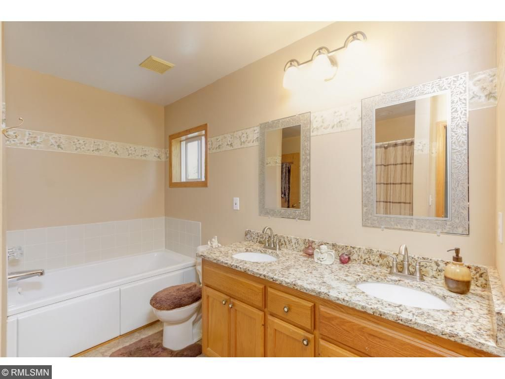 The double sink, contemporary vanity and faucet with classic white tile tub beautifully decorates this bathroom.