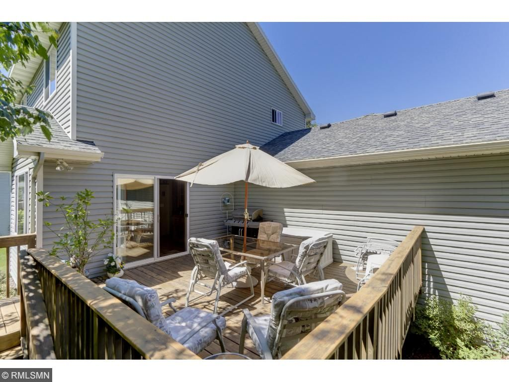 This spacious deck offers ample room for a sitting area and barbecue. The view from the deck reveals sprawling, emerald lawn!