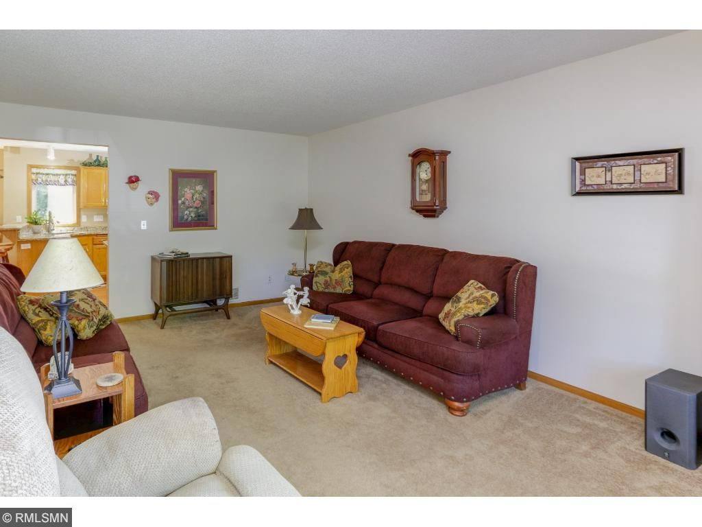 Plush carpeting that lines the living room adds coziness and intimacy to the space.