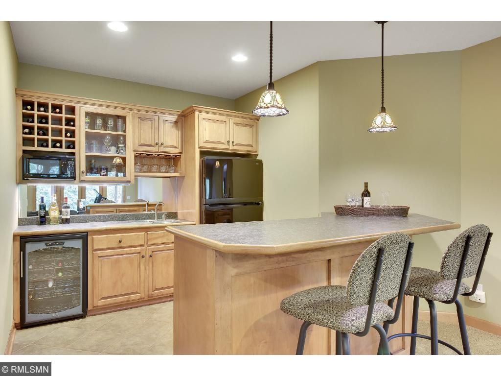 The Wet bar provides birch cabinetry, coffee station, wine refrigerator, full-size refrigerator and microwave.  The lower level also offer in-floor heat!