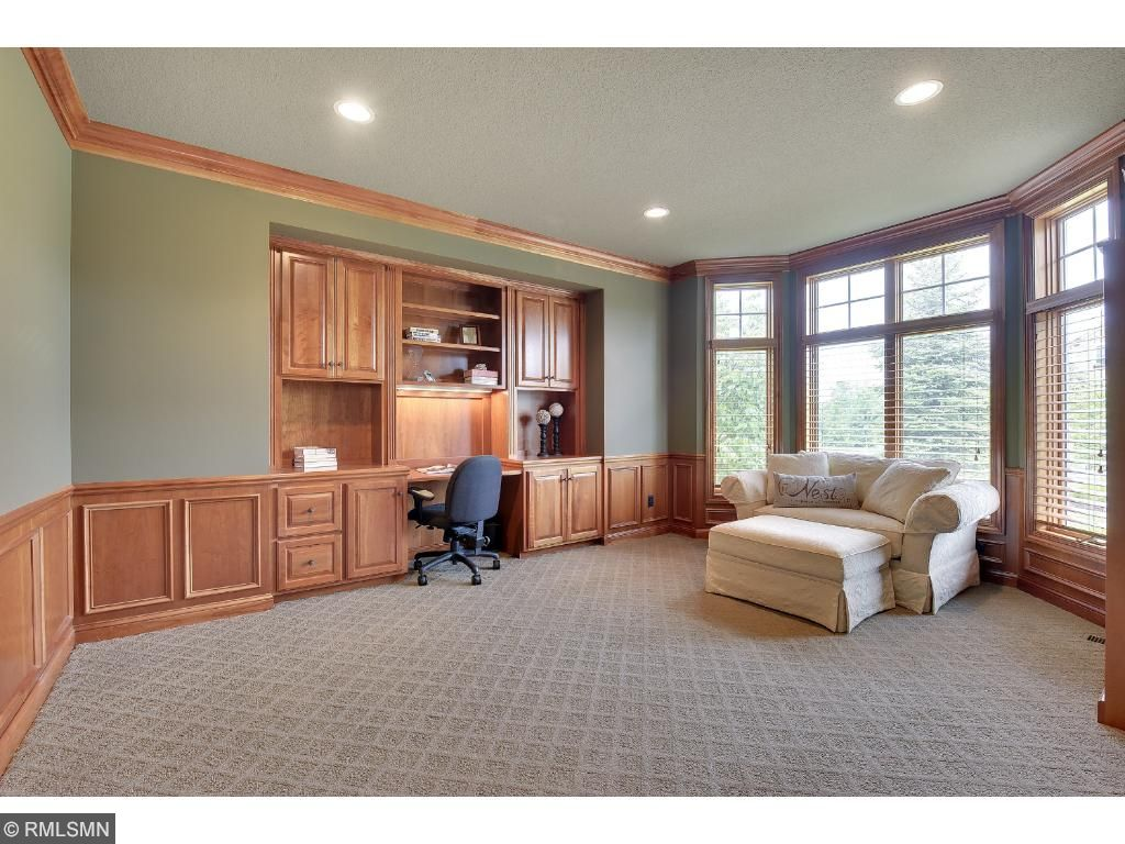 The office provides 14' door, crown molding, Cherry wainscoting along with built-in desk and cabinetry.