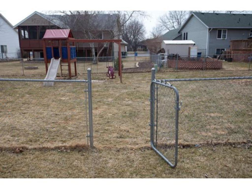 The large fenced backyard boasts a play set that is staying with the home