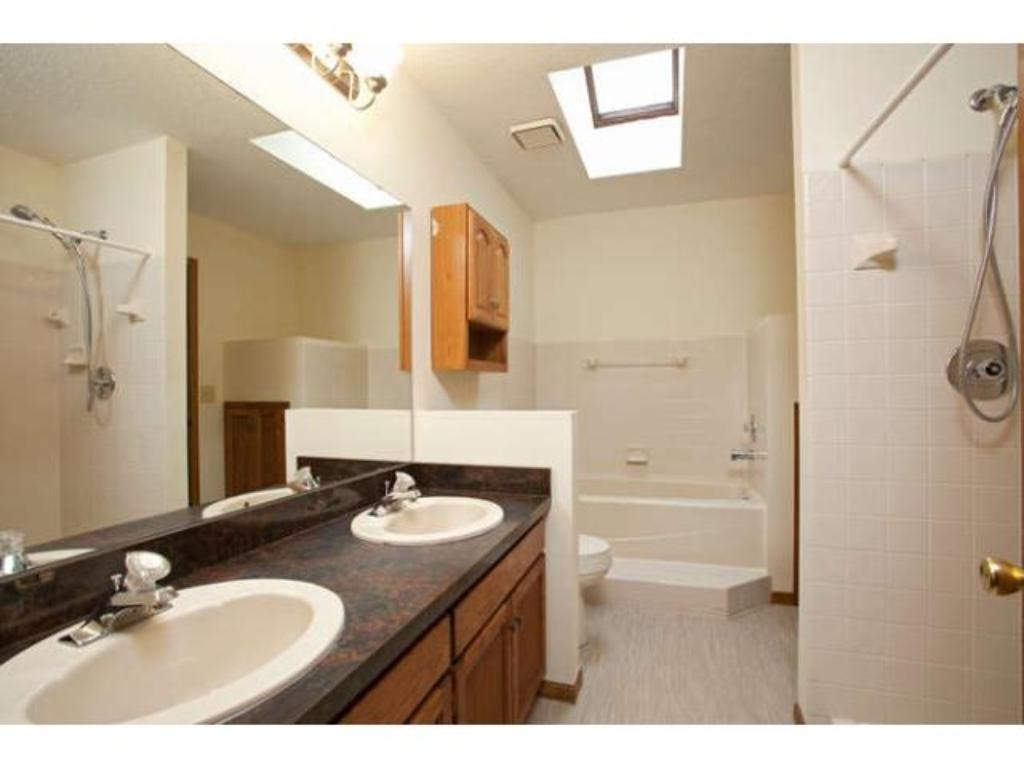 Walk-through Bath boasts double sinks, separate tub and shower, new flooring, and a sky light