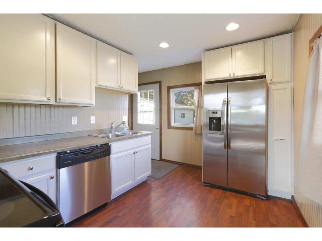 The kitchen has been nicely updated and features newer stainless steel appliances and modern white cabinetry.