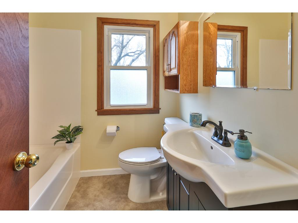 The updated main level full bath includes new toilet, flooring, sink, vanity, faucet and fresh paint.