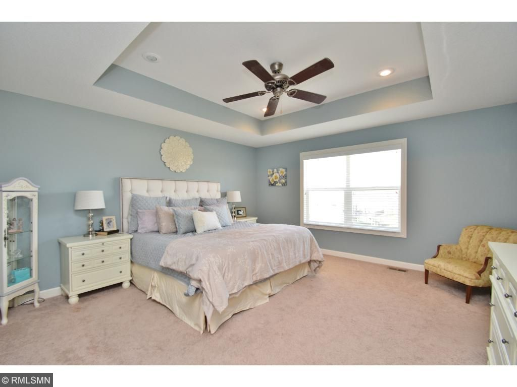 Master bedroom is beautiful -- soothing color scheme, tray ceiling, ceiling fan, even room for a chaise lounge and more!