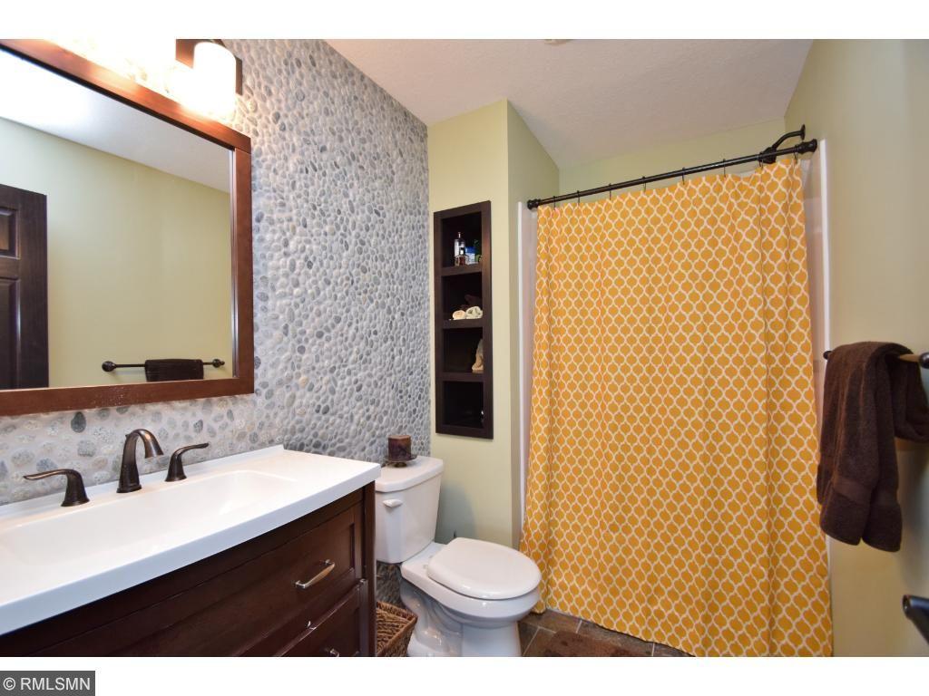 Lower level three-quarter bathroom with unique stone wall.